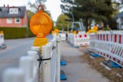 Barriere rosse e bianche con le luci d'avvertimento ad una via in Immagini Stock Libere da Diritti