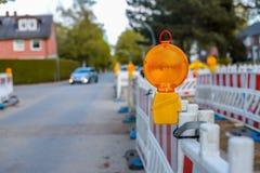 Barriere rosse e bianche con le luci d'avvertimento ad una via in Fotografie Stock Libere da Diritti