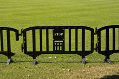 Stop. Barriers on green. A line of black plastic barriers, limiting access to the field Stock Image
