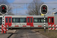 Barriers and red traffic lights at a crossing with the subway at station De Tochten in Rotterdam Zevenkamp in the Netherlands. Barriers and red traffic lights stock photos