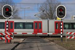 Barriers and red traffic lights at a crossing with the subway at station De Tochten in Rotterdam Zevenkamp in the Netherlands. Barriers and red traffic lights royalty free stock images