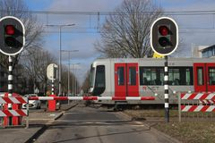 Barriers and red traffic lights at a crossing with the subway at station De Tochten in Rotterdam Zevenkamp in the Netherlands. Barriers and red traffic lights royalty free stock image