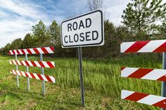 Barriers With Road Closed Sign. Horizontal angled shot of red and white striped barriers with a road closed sign in the middle of them in a wooded area royalty free stock photo