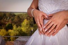 A barriga da menina grávida as mãos dos homens e das mulheres no abdômen foto de stock