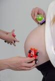 Barriga da mulher gravida com carros do brinquedo imagem de stock