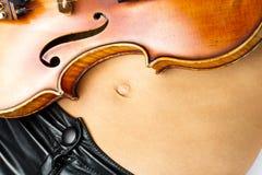 Barriga da mulher nova com o violino nele Fotos de Stock