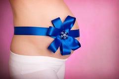 Barriga das mulheres gravidas no rosa Imagens de Stock Royalty Free