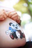 Barriga de uma mulher gravida em um fundo claro Fotografia de Stock Royalty Free