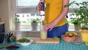 A barriga e as mãos da mãe expectante misturam o leite e o cocktail de frutos orgânico com o misturador filme