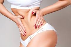A barriga fêmea gorda, mulher que guarda sua pele para celulites verifica Fotografia de Stock
