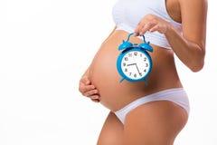 Barriga grávida com despertador Imagem conceptual Logo nascimento imagens de stock