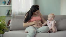 A barriga grávida da mamã tocante do bebê curioso, esperando a irmã mais nova ou o irmão video estoque