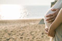 Barriga grávida pelo mar foto de stock royalty free