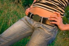 Barriga 'sexy' do tan da mulher do close up nas calças de brim Imagens de Stock Royalty Free