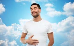 Barriga tocante do homem completo feliz sobre o céu azul fotografia de stock royalty free
