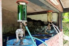 Barril de aceite del surtidor de gasolina del vintage, bomba de aceite manual rotatoria de la mano en el campo imagen de archivo libre de regalías