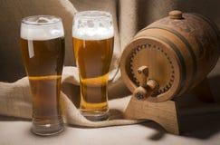 Barril de madera con los vidrios de cerveza en fondo de la lona Fotografía de archivo
