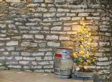 Barril de madera viejo y árbol de navidad iluminado Imagen de archivo libre de regalías