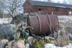 Barril oxidado contra un fondo de la casa de madera vieja fotos de archivo libres de regalías