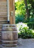 Barril para agua de madera que recoge la salida del tejado a través de los canales Fotos de archivo libres de regalías