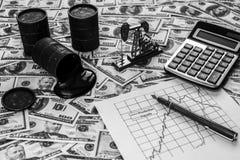 Barriles con aceite, una calculadora, un neftechka, un horario de importaciones de petróleo y exportaciones contra foto de archivo libre de regalías