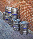 Barriles de cerveza de aluminio contra una pared de ladrillo Foto de archivo