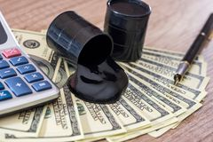 Barriles de petróleo con el dinero del dólar en el escritorio de madera fotos de archivo