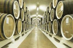 Barriles de vino almacenados en el sótano foto de archivo