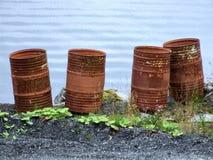 Barriles inútiles oxidados viejos por el mar Fotografía de archivo