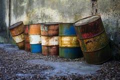 Barriles inútiles oxidados viejos por el mar foto de archivo