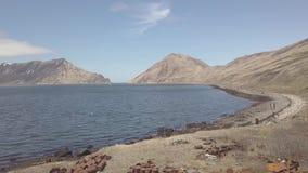 Barriles oxidados de la visión aérea en paisaje de la playa y de la montaña del mar en destruido almacen de video