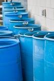 Barriles para agua azules en una fila que fluye en uno a Imagen de archivo