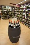 Barriles y estantes de la tienda de las botellas de vino Foto de archivo