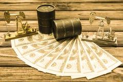 Barris de petróleo, dólares americanos, neftechka em um fundo de madeira , imagem de stock