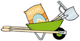Barrow with seeds, a rake and shovel. Green wheelbarrow with garden tools and seeds Stock Photo