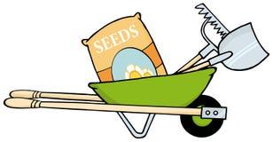 Barrow with seeds, a rake and shovel Stock Photo