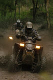 Barry Mud 02. Two Quad bike racers (ATV) blast through a muddy hole Royalty Free Stock Images