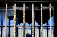 Bars on Broken Window. Security bars on broken window to prevent breaking into building Stock Images