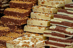 Bars of classical and white chocolate, with nuts pieces. Exposed to sale in bulk Stock Images