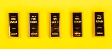 Bars of gold bullion on yellow background stock image