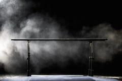 bars gymnastisk parallel på svart bakgrund med dimma, arkivfoton