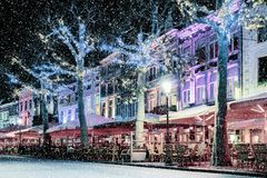 Bars and restaurants with snow and christmas lights on the famous Vrijthof square in Maastricht royalty free stock images