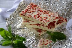 Bars of White Chocolate with Dried Strawberry. Irregular shapes of white chocolate bars mixed with finely diced dried strawberry pieces. Stacked on a crumpled Royalty Free Stock Photo