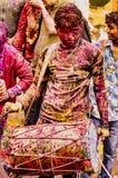 Barsana, Inde/le 23 février 2018 - un batteur bat un air pour les noceurs tandis que couvert en peinture dans le festival de Holi image libre de droits