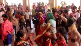 Barsana, India - 20180223 - Holi-Festival - de Moeder houdt Kind in Midden van het Dansen Menigte stock footage