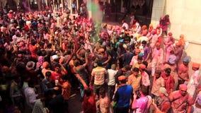 Barsana, India - 20180223 - Holi-Festival - van Bovengenoemd wordt gezien - Menigte werpt Wapens in Lucht in Dans die stock video