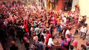 Barsana, India - 20180223 - Holi-Festival - van Bovengenoemd wordt gezien - wordt Verf geworpen aangezien de Menigte Wapens in Lu stock videobeelden