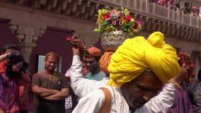 Barsana, la India - 201802242 - festival de Holi - caos - vueltas del hombre con las flores en su cabeza almacen de metraje de vídeo