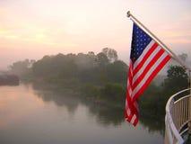 Barsk flagga och flodfördämning i misten Arkivbild
