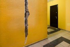 Barst in de muur van het flatgebouw Gele muur in de ingang stock afbeelding